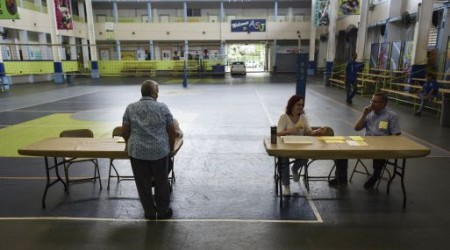 Puerto Rican citizens register before they can exercise their vote during the fifth referendum in San Juan, Puerto Rico, Sunday, June 11, 2017. Puerto Ricans are getting the chance to tell U.S. Congress on Sunday which political status they believe best benefits the U.S. territory as it remains mired in a deep economic crisis that has triggered an exodus of islanders to the U.S mainland. Congress ultimately has to approve the outcome of Sunday's referendum that offers voters three choices: statehood, free association/independence or current territorial status. (AP Photo/Carlos Giusti)