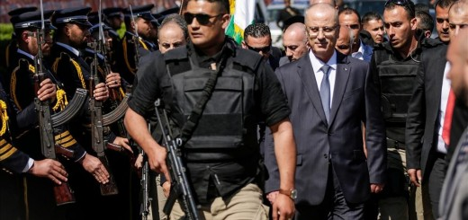 Palestinian Prime Minister Rami Hamdallah  2nd-R   escorted by his bodyguards  is greeted by police forces of the Islamist Hamas movement  L  upon his arrival in Gaza City on March 13  2018    AFP PHOTO   MAHMUD HAMS