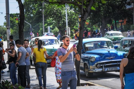 A Cuban man takes a picture with his mobile phone in a street of Havana, on July 2, 2015. Cuban state-owned telecommunications company Etecsa opened 35 public Wi-Fi areas in the country and lowered the rate of connections to half the price in an effort to expand the limited connectivity on the island. AFP PHOTO/YAMIL LAGE (Photo credit should read YAMIL LAGE/AFP/Getty Images)