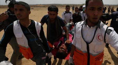 A wounded Palestinian is evacuated during a protest against U S embassy move to Jerusalem and ahead of the 70th anniversary of Nakba at the Israel-Gaza border in the southern Gaza Strip May 14 2018 REUTERS Ibraheem Abu Mustafa