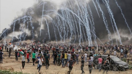 TOPSHOT - Palestinian protesters flee from incoming teargas canisters during clashes with Israeli forces along the border with the Gaza strip east of Gaza City on May 4 2018 on the sixth straight Friday of mass demonstrations calling for the right to return to their historic homelands AFP PHOTO MAHMUD HAMS