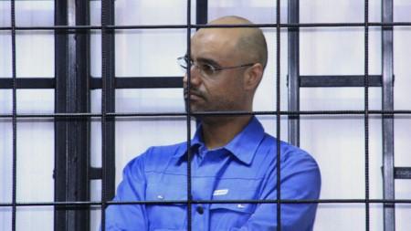 Saif al-Islam Gaddafi, son of late Libyan leader Muammar Gaddafi, attends a hearing behind bars in a courtroom in Zintan May 15, 2014. REUTERS/Stringer (LIBYA - Tags: POLITICS CIVIL UNREST) - RTR3PCA8