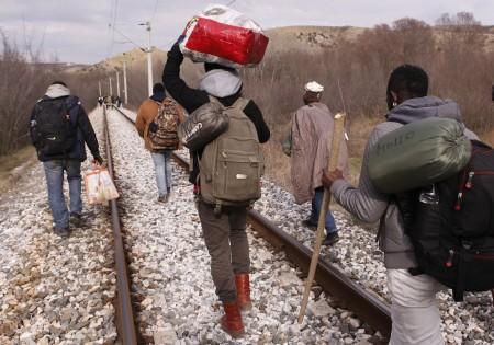 Emigrantes africanos caminan junto a las vías de un tren durante una travesía a pie de 250 kilómetros por la frontera entre Grecia y Macedonia, que es el tramo más duro de una nueva ruta hacia la Unión Europea por los Balcanes. Foto del 28 de febrero del 2015 tomada cerca de Evzonoi, Grecia. (AP Photo/Dalton Bennett)
